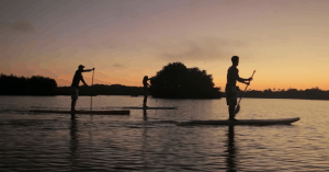 a picture of paddle boarding at sunset